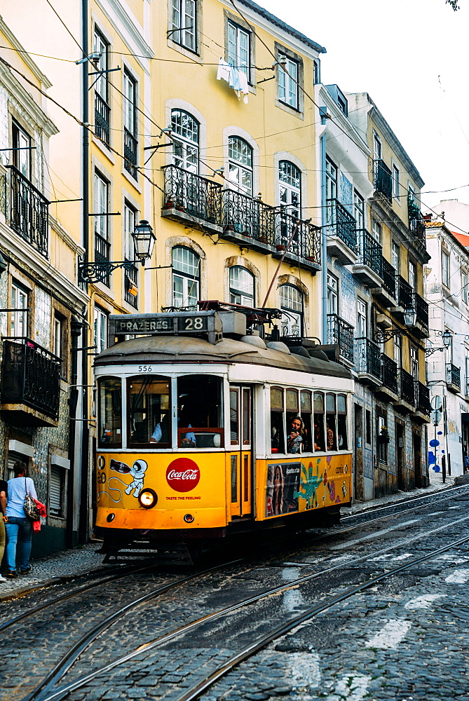 Traditional yellow electric tram in a narrow street in Alfama, Lisbon, Portugal, Europe - 1243-353
