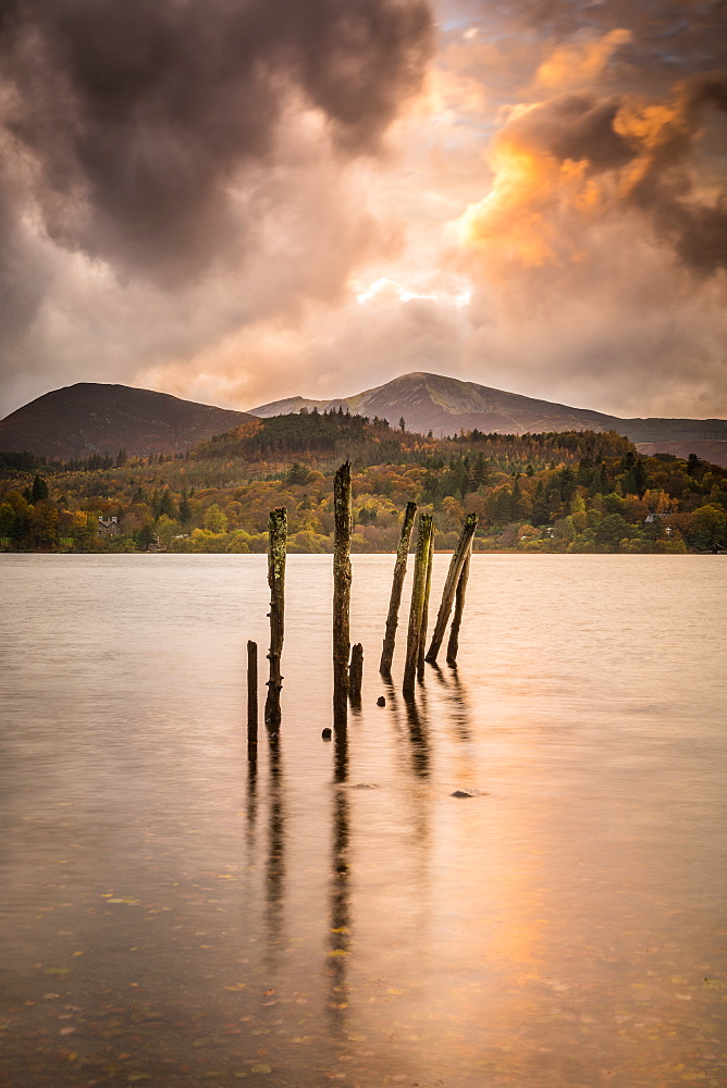 The old jetty posts on the shores of Derwent Water as the last rays of sunlight finally burst through the thick cloud, Lake District National Park, Cumbria, England, United Kingdom, Europe