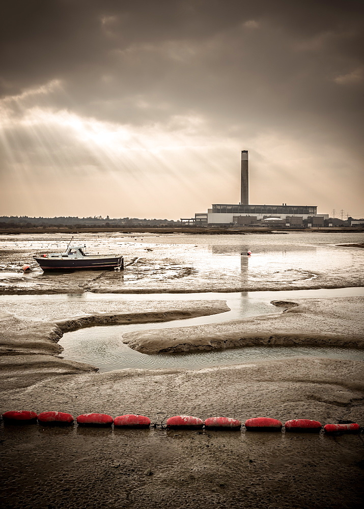 Boat and Power Station. Fawley power station, a boat and a creek meandering through the mudflats all lit by a broken sky.