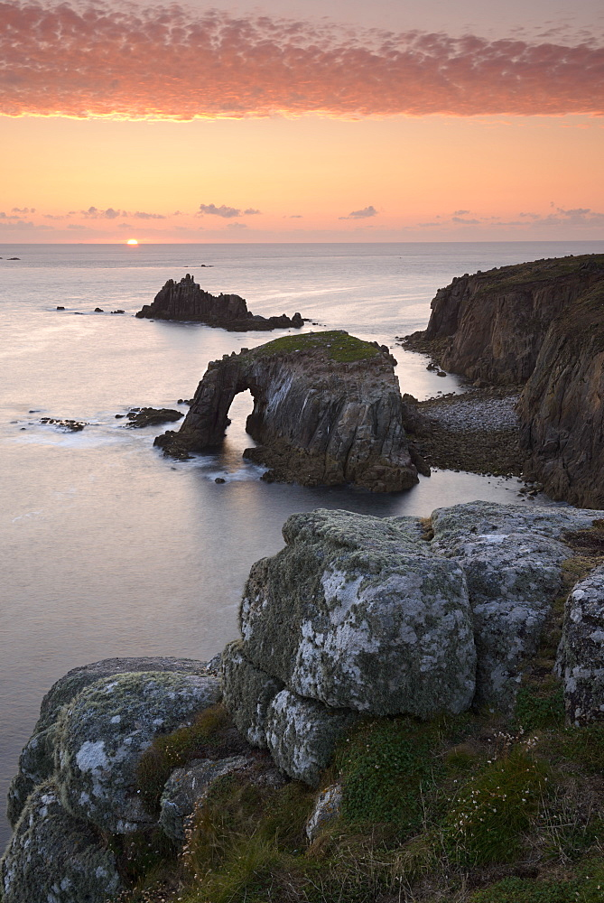 A colourful sunset overlooking the islands of Enys Dodnan and the Armed Knight at Land's End, Cornwall, England, United Kingdom, Europe
