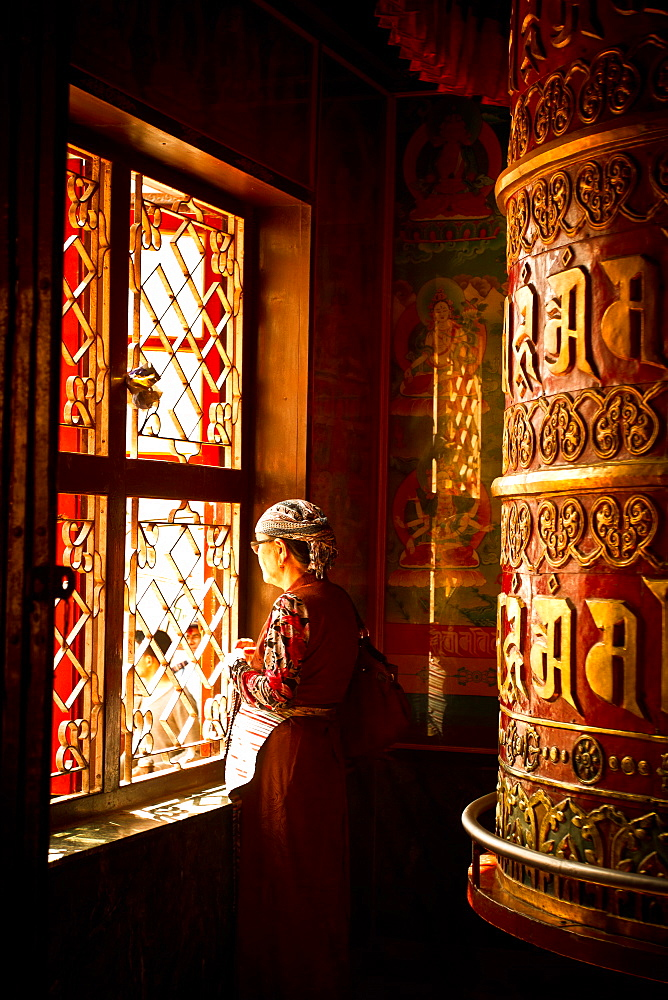 A Tibetan woman stands next to a large prayer wheel of the temple of Boudhanath Stupa, Kathmandu, Nepal, Asia