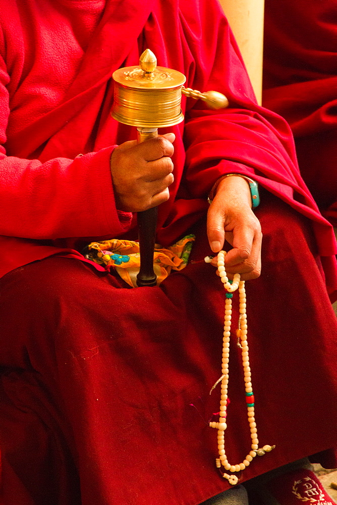 Tibetan Buddhist monk with prayer wheel and beads at Losar (Tibetan New Year) in the Dalai Lama Temple, McLeod Ganj, Dharamsala, Himachal Pradesh, India, Asia