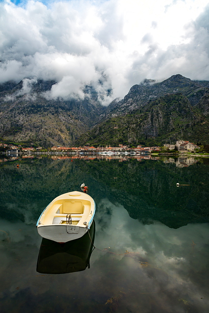 A small fishing boat sits in the reflection of the Old Town (stari grad) of Kotor in Kotor Bay, UNESCO World Heritage Site, Montenegro, Europe - 1263-17