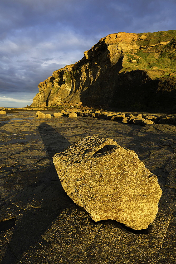 Geology and cliffs lit by low angled evening sunlight at Saltwick Bay on the East Coast, North Yorkshire, England, United Kingdom, Europe - 1266-17