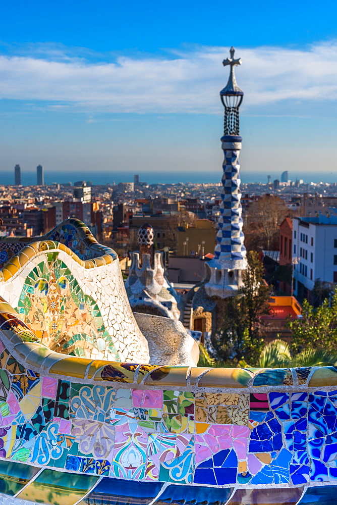 Park Guell houses and mosaic tiles at Parc Guell, with views over the city to the sea, by Gaudi. Barcelona, Catalonia, Spain.