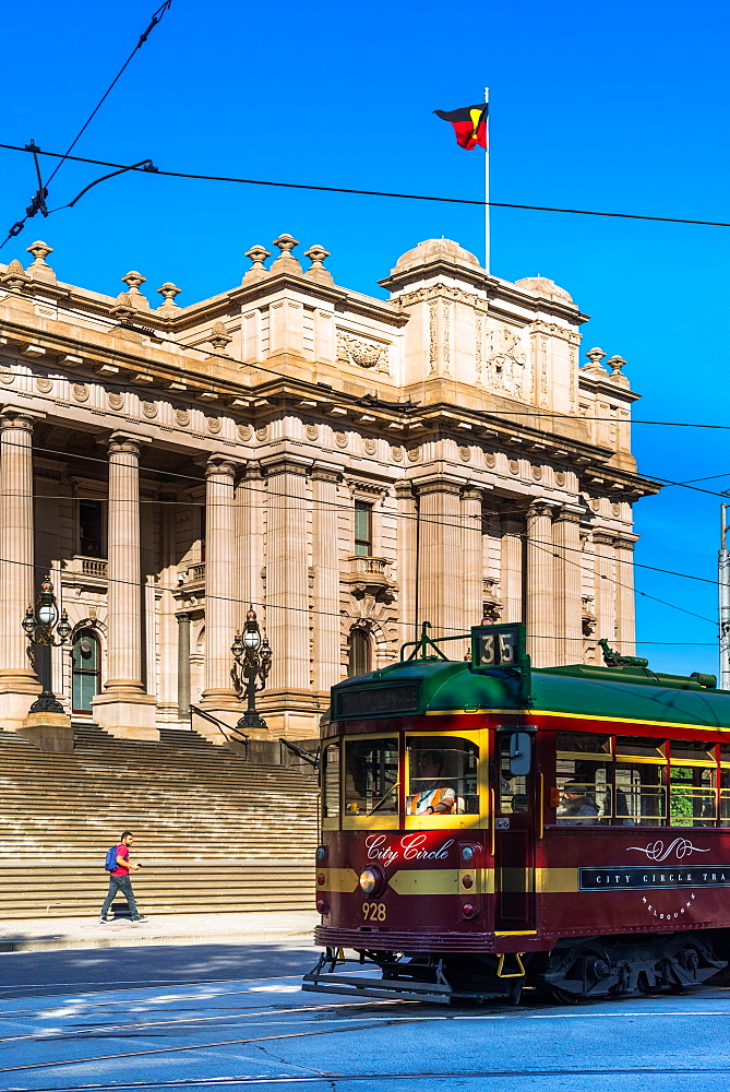 A classic tram goes past Parliament House in Melbourne, Victoria, Australia.