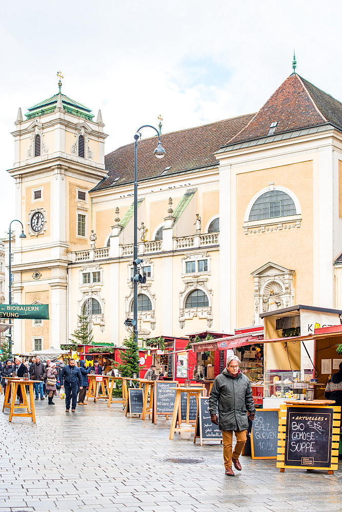 The Freyung Christmas market with Schottenkirche Catholic Church to the rear, Vienna city centre, Austria.