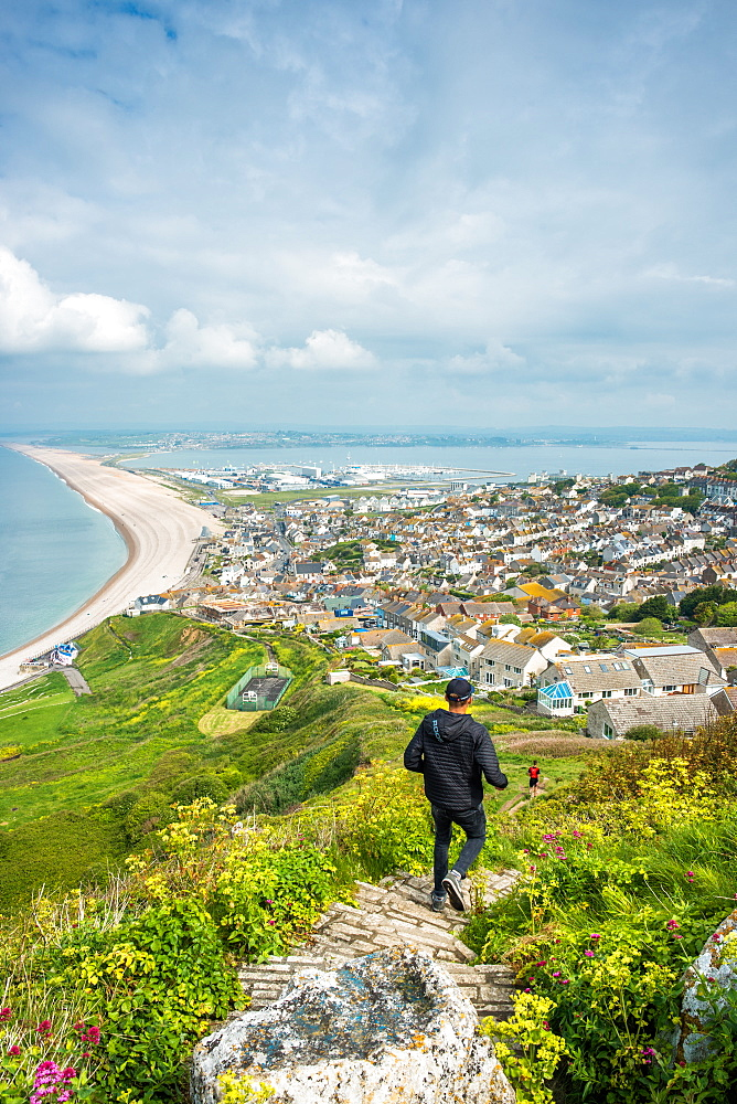 Joggers take the path down to Chesil Beach from Portland heights on the Isle of Portland, Dorset, England, UK.