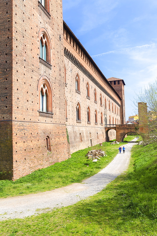 Two person walks in the park of Castello Visconteo(Visconti Castle). Pavia, Pavia province, Lombardy, Italy, Europe