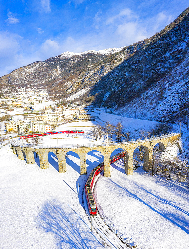 Bernina Express passes under the helical (spiral) viaduct of Brusio, UNESCO World Heritage Site, Valposchiavo, Canton of Graubunden, Switzerland, Europe