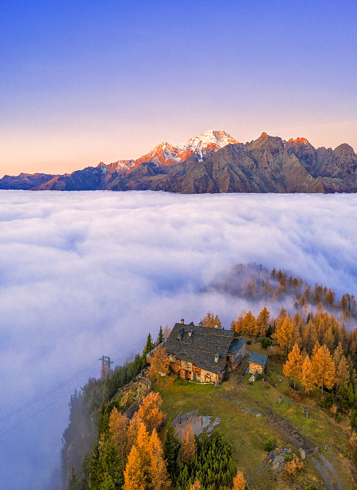 Fog covers the Valmalenco (Val Malenco) with Mount Disgrazia illuminated by sunrise and the Motta hut, Valtellina, Lombardy, Italy, Europe - 1269-628