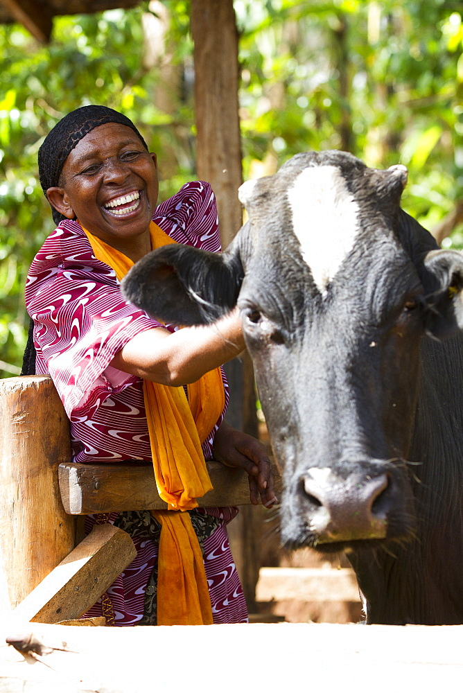 A woman smiling next to her cow, Uganda, Africa