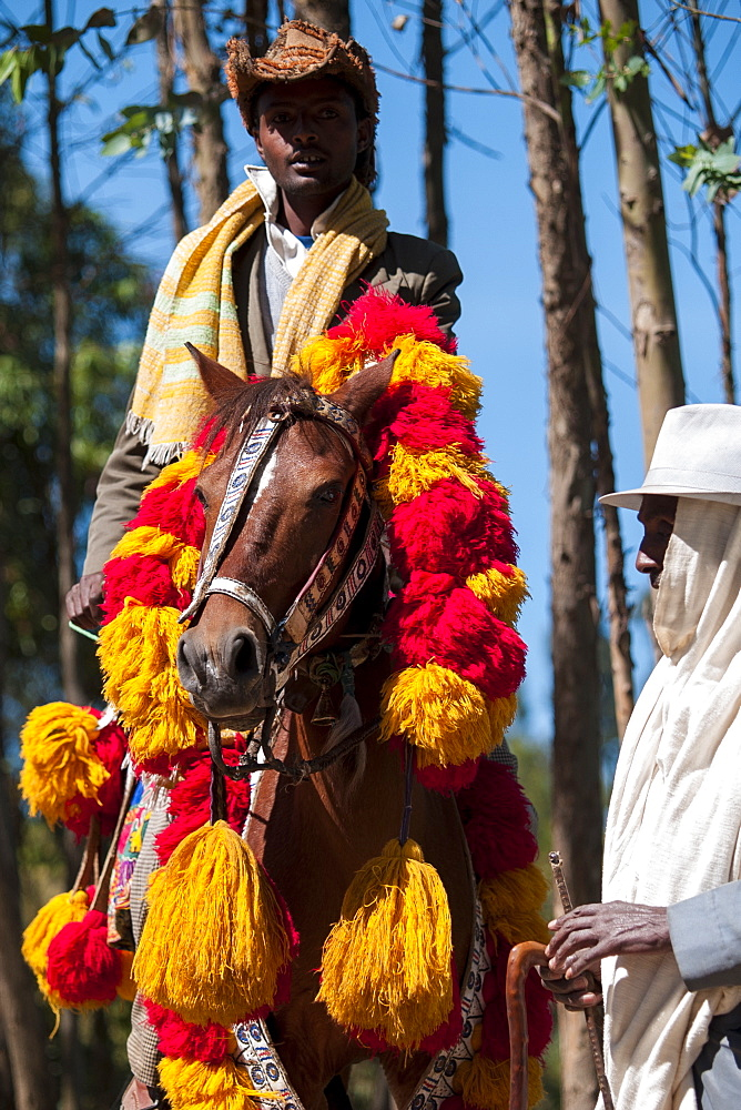 A man rides his horse with traditional red and yellow Ethiopian headdress.