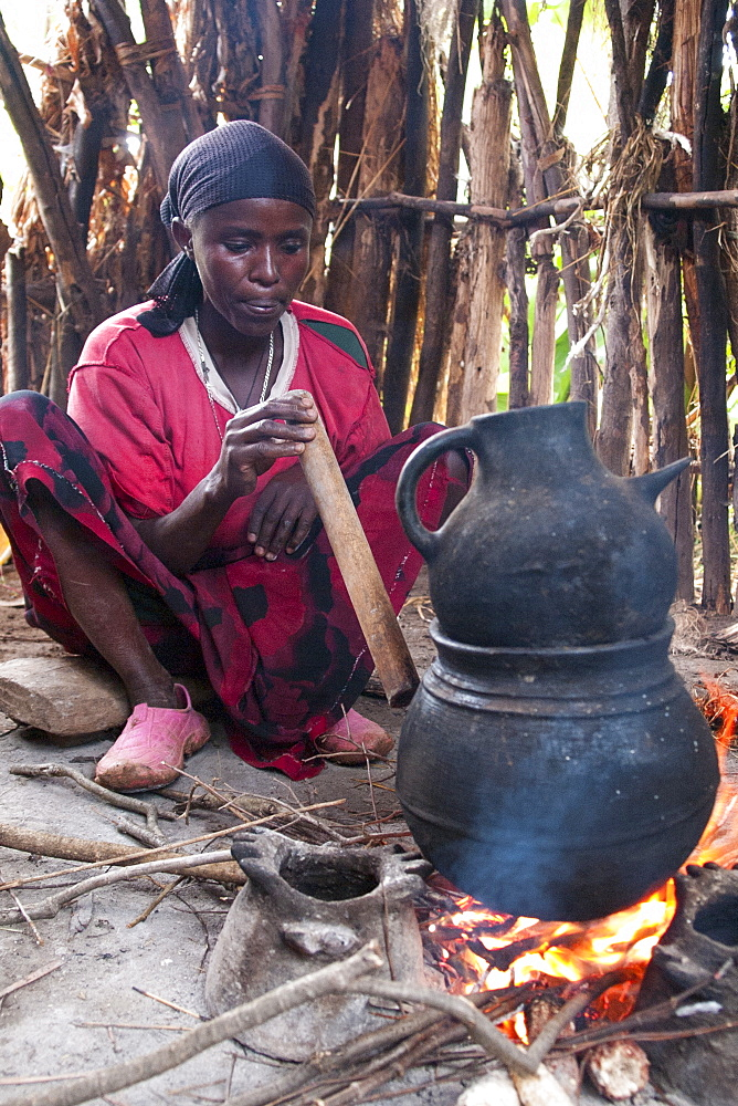 A woman blows through a wooden pipe to get the fire going whilst brewing some coffee on an open fire, Ethiopia, Africa