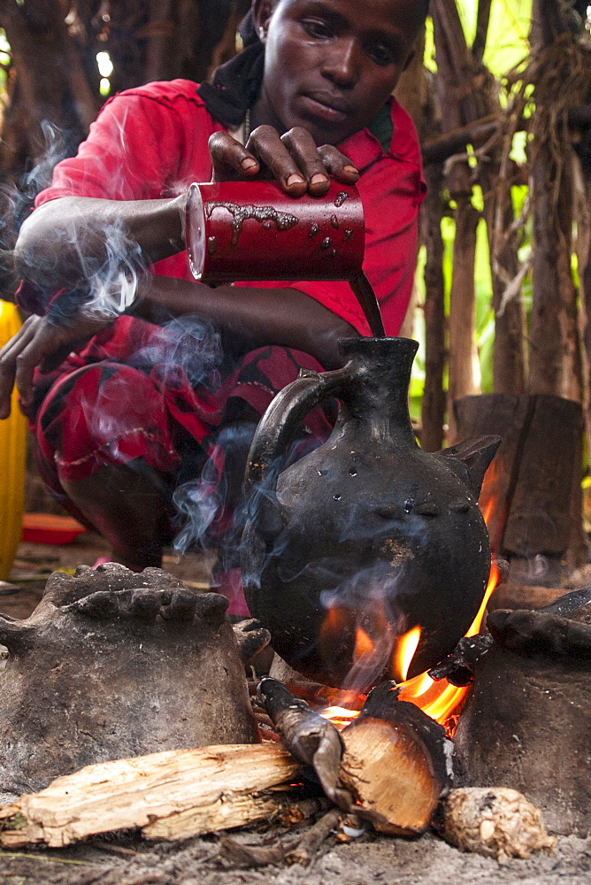 A woman pours into a traditional Ethiopian coffee pot on an open fire, Ethiopia, Africa - 1270-48