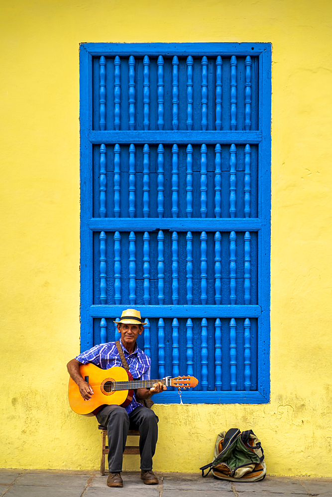 An elderly Cuban sitting on a chair. playing a guitar, Trinidad, Sancti Spiritus Province, Cuba, Central America
