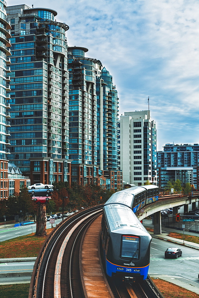 Sky Train metro, apartment buildings and Cars stacked as modern art exhibition, Vancouver, Canada, British Columbia, America.