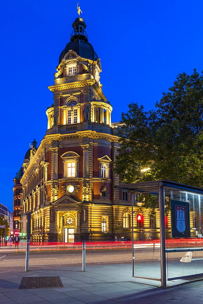 Illuminated Alte Oberpostdirektion building in Hamburg at dusk