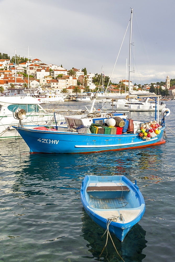 Colorful boat anchoring in the port of Hvar Town with view to the old town in the background