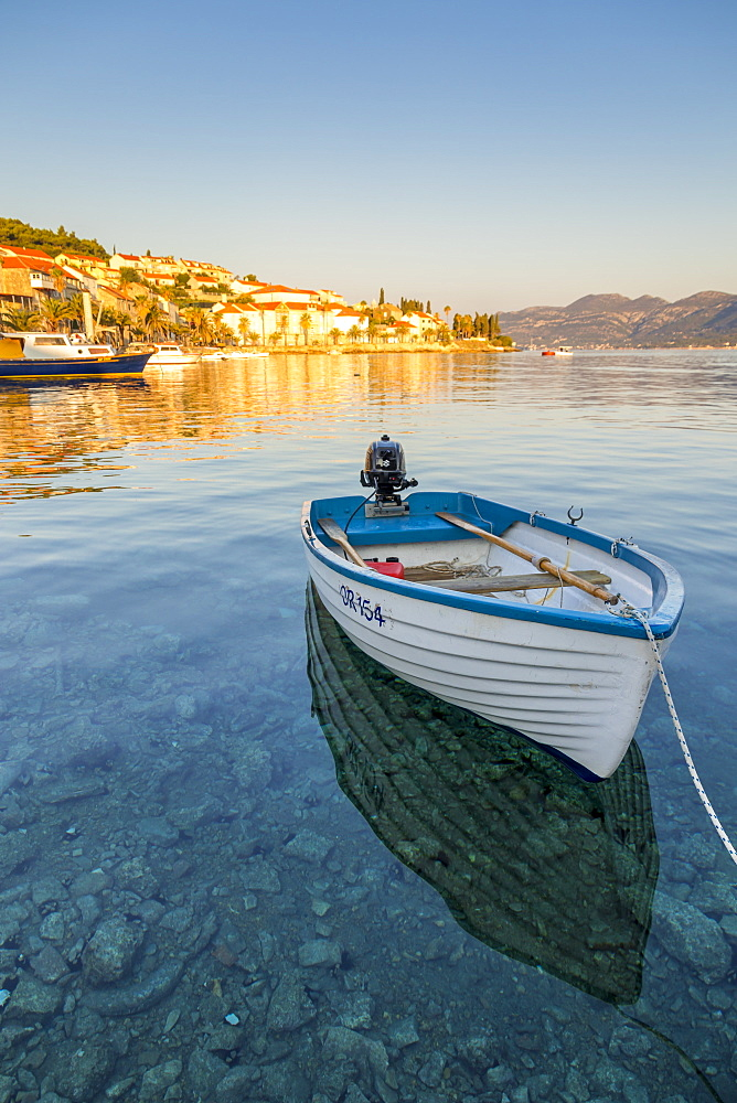 Small boat anchoring outside the old town at first sunlight, Korcula Town, Croatia