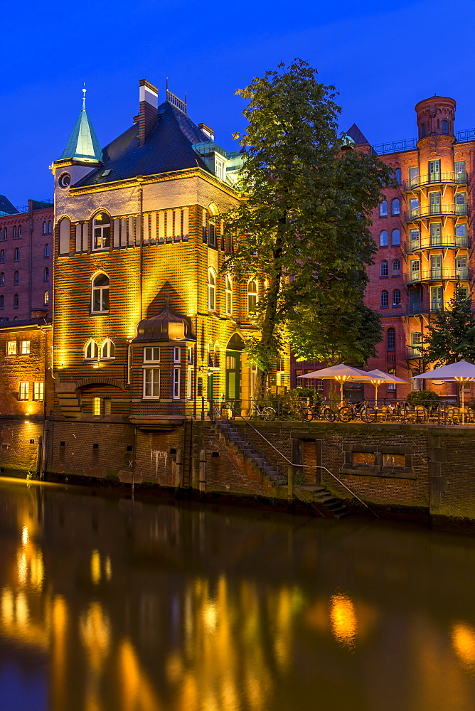 Illuminated Wasserschlösschen building in the historical Speicherstadt (Warehouse complex) of Hamburg at dusk