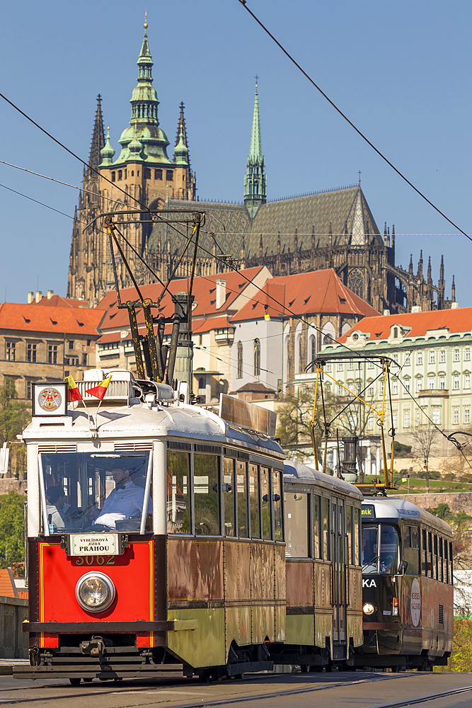 Tourist tram passing a bridge over Vltava River with view to Prague Castle in the background, Prague, Bohemia, Czech Republic, Europe