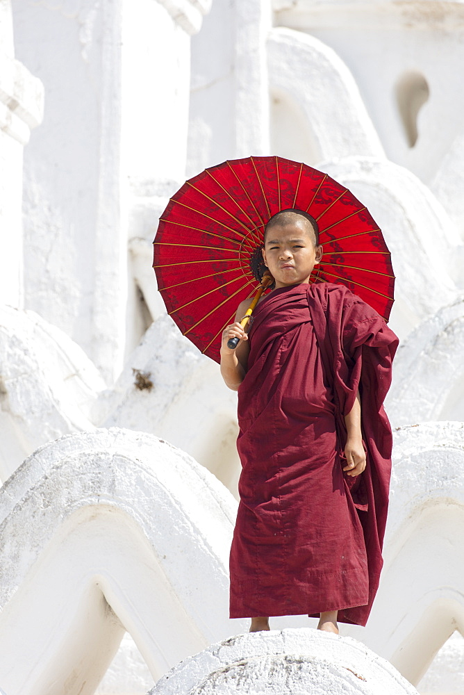 Young monk dressed in red, with red parasol at the Myatheindan Pagoda (White Temple) in Mingun, Myanmar (Burma), Asia