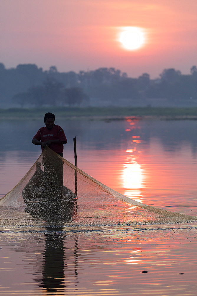 Fisherman casts his net at sunrise on lake Taungthaman near U Bein Bridge, Myanmar (Burma)