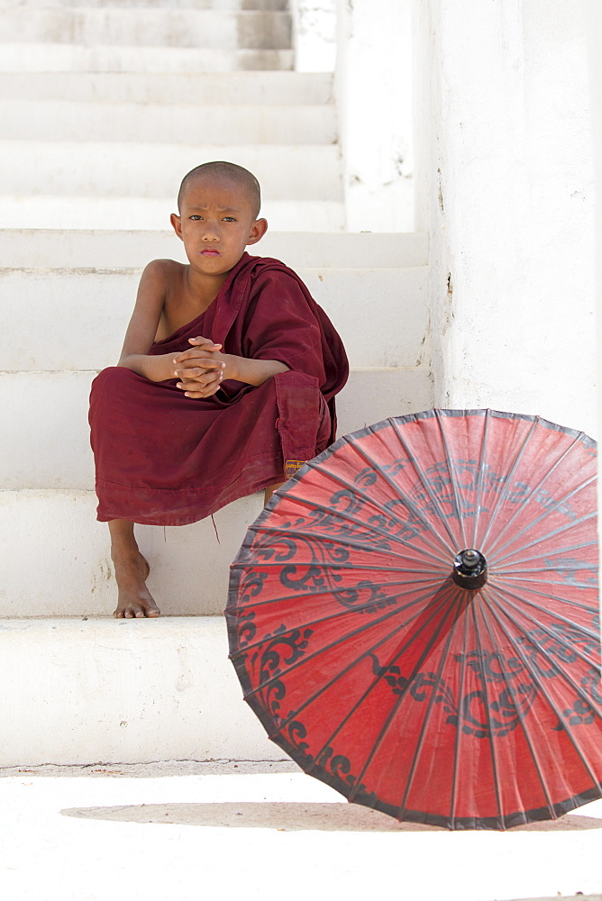 Young monk dressed in red, sits on steps with red parasol at the Myatheindan Pagoda (White Temple) in Mingun, Myanmar (Burma), Asia