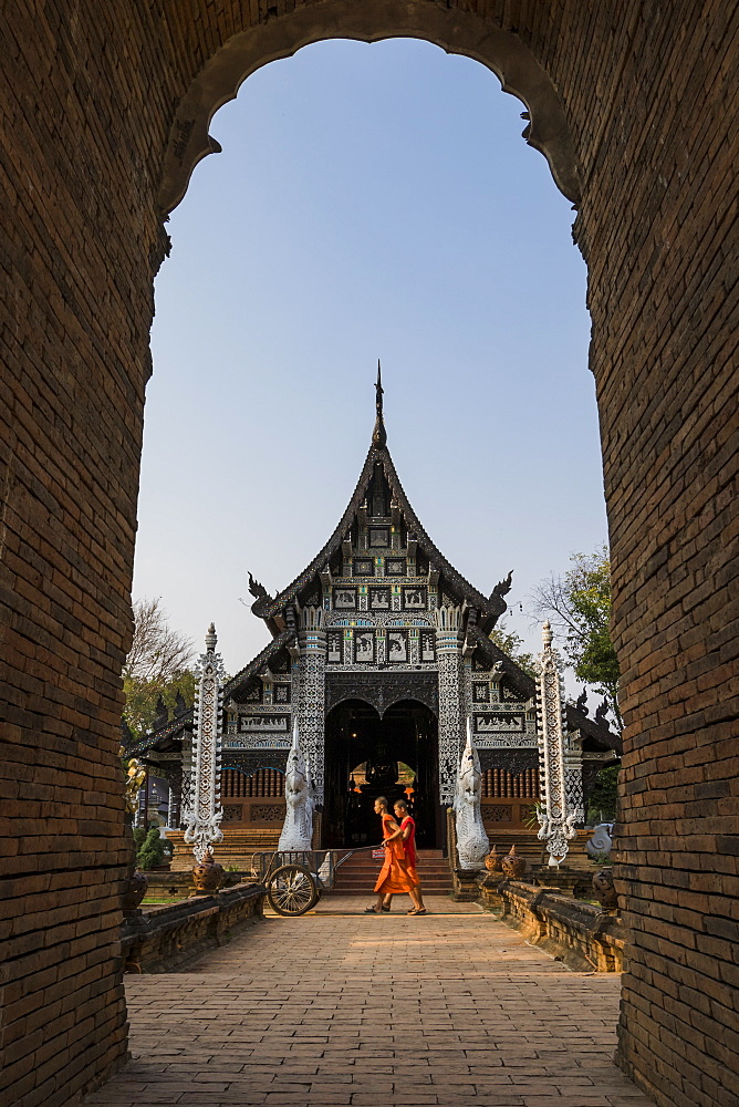 Temple Wat Lok Moli seen through an arch with two monks walking by, Chiang Mai, Thailand, Southeast Asia, Asia - 1286-60