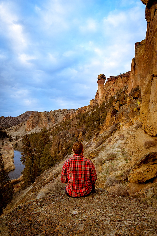 Man wearing a flannel shirt looking at a large rock formation, Oregon, United States of America, North America - 1289-10