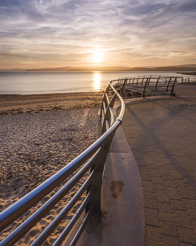 The sun sets in line with railings on the slipway at the RNLI station, Exmouth, Devon, England, United Kingdom, Europe