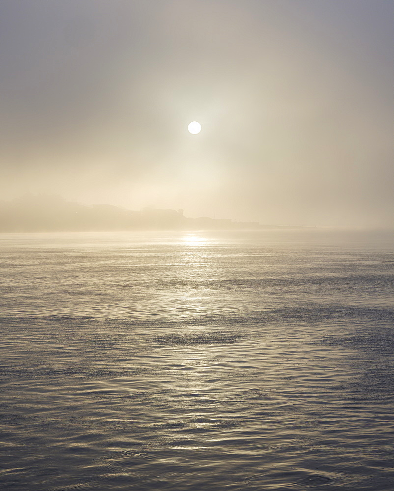 The sun shines through heavy fog on the sea front at Exmouth, Devon, England, United Kingdom, Europe - 1295-110