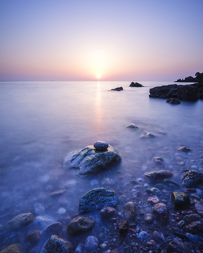 A colourful spring sunrise over Torbay with warm light glinting off the wet rocks, Anstey's Cove, Torquay, Devon, England, United Kingdom, Europe