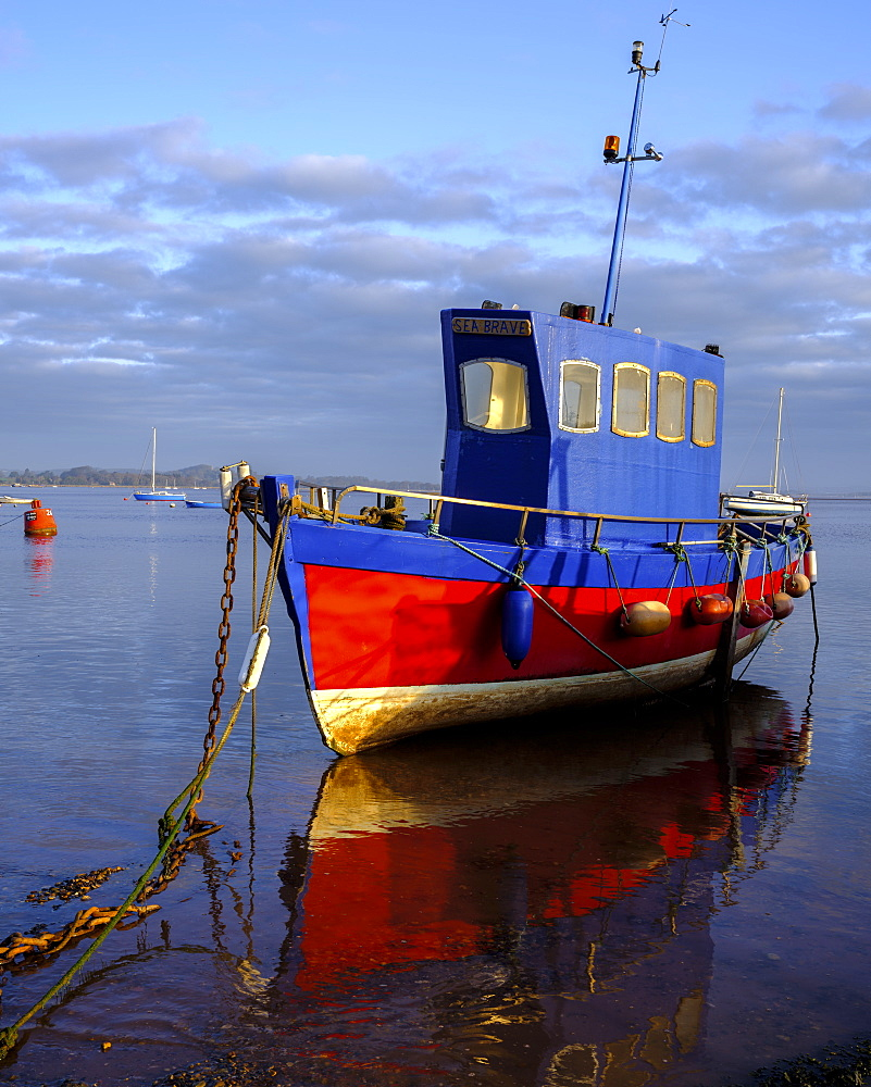Boat moored on the shoreline of the calm Exe Estuary, Exmouth, Devon, England, United Kingdom, Europe - 1295-23