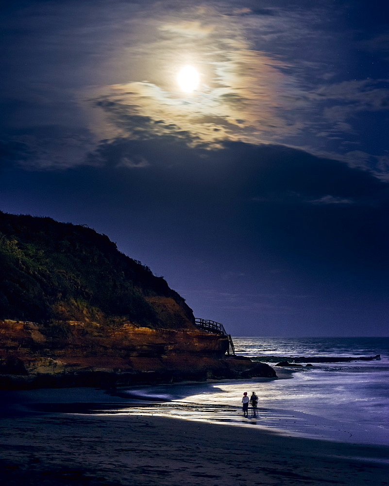Two ladies paddle whilst watching the full Blood Moon, shortly after an eclipse at Orcombe Point, Exmouth, Devon, England, United Kingdom, Europe - 1295-29