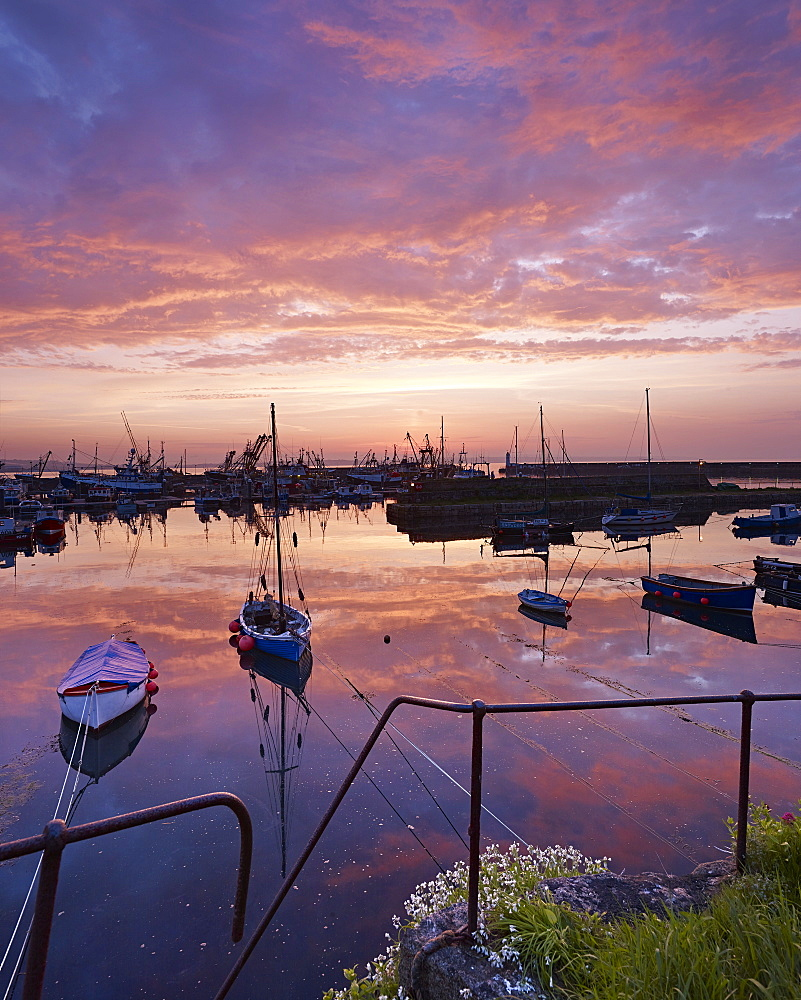 Dawn twilight with underlit clouds, reflections and moored boats in the harbour of the fishing port of Newlyn in Cornwall, UK.
