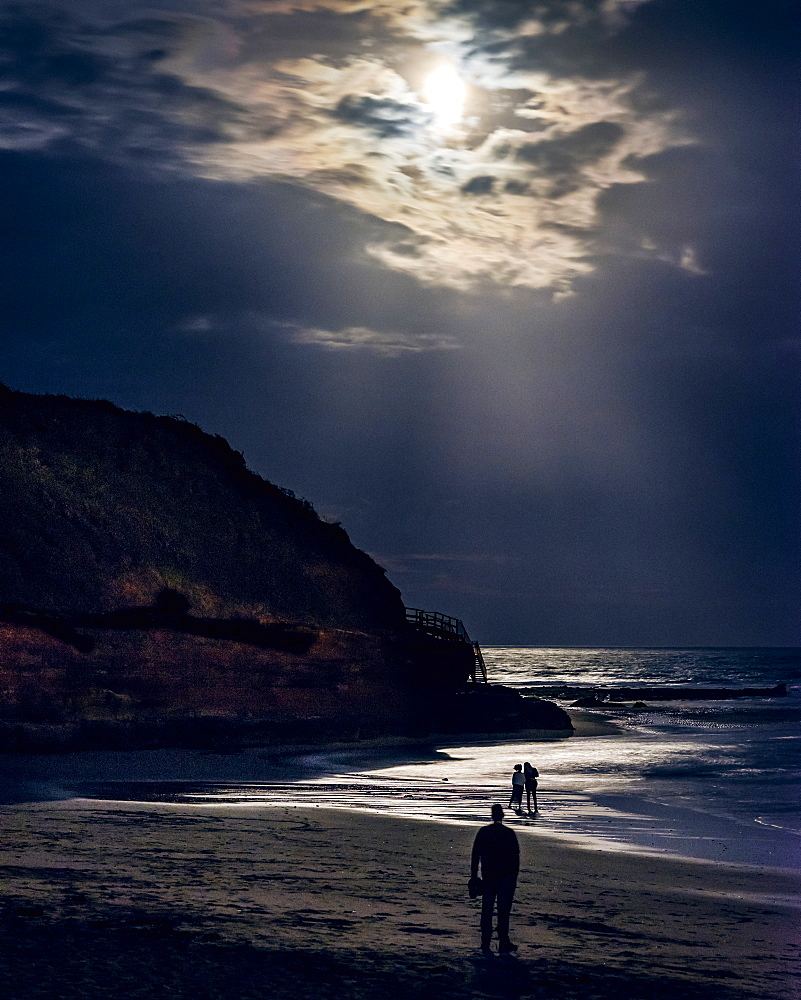Someone observes two ladies whilst watching the full Blood Moon, shortly after an eclipse at Orcombe Point, Exmouth, Devon, England, United Kingdom, Europe - 1295-30