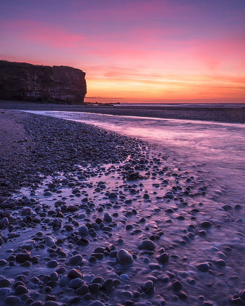 The River Otter meets the sea with strong dawn colour, wet pebbles and the cliff of Otter Head at Budleigh Salterton, Devon, England, United Kingdom, Europe