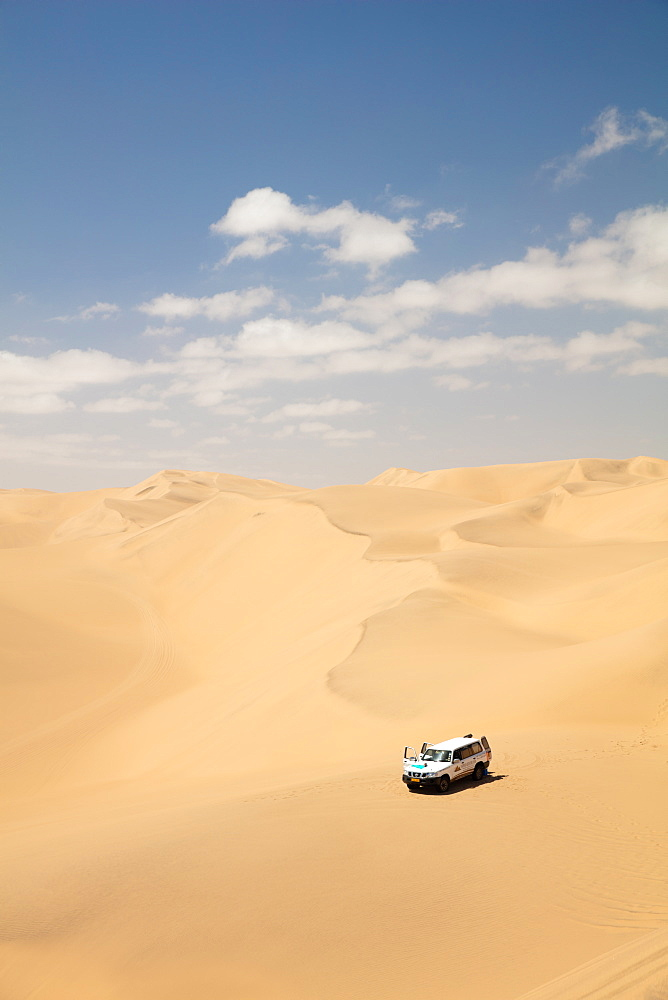 A car pictured within the Sandwich Harbour dunes, Skeleton Coast at midday, Namibia, Africa - 1304-34