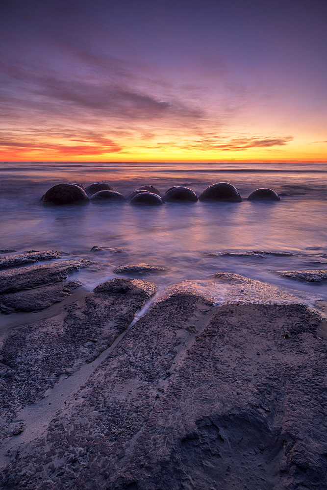Epic sunrise at Moeraki Beach with the Moeraki Boulders, Moeraki Beach, Otago, New Zealand.
