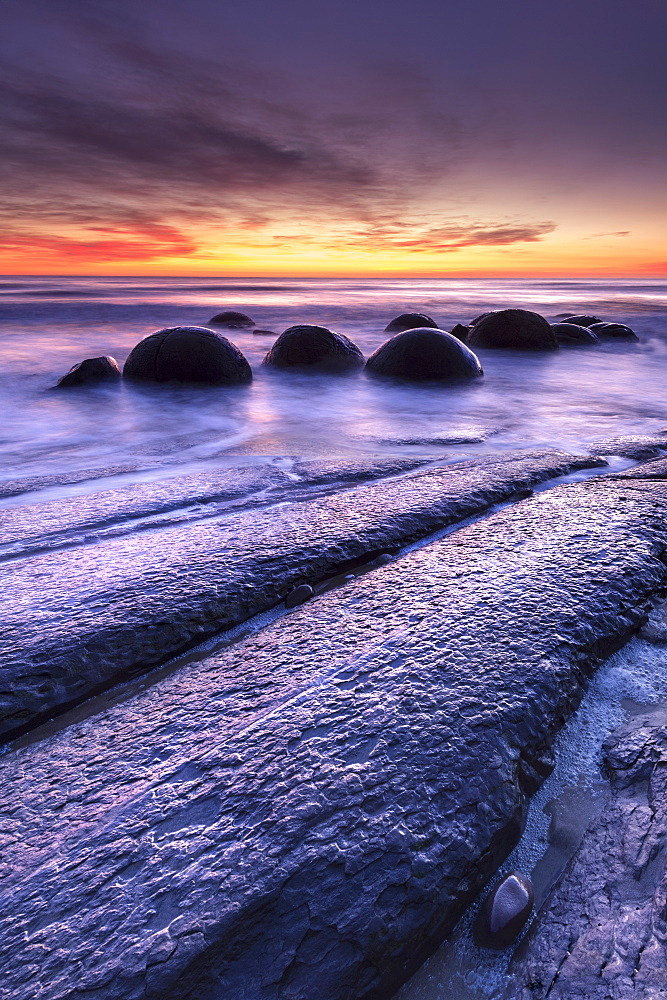 The Moeraki Boulders with dramatic sunrise at Moeraki Beach, Otago, New Zealand.