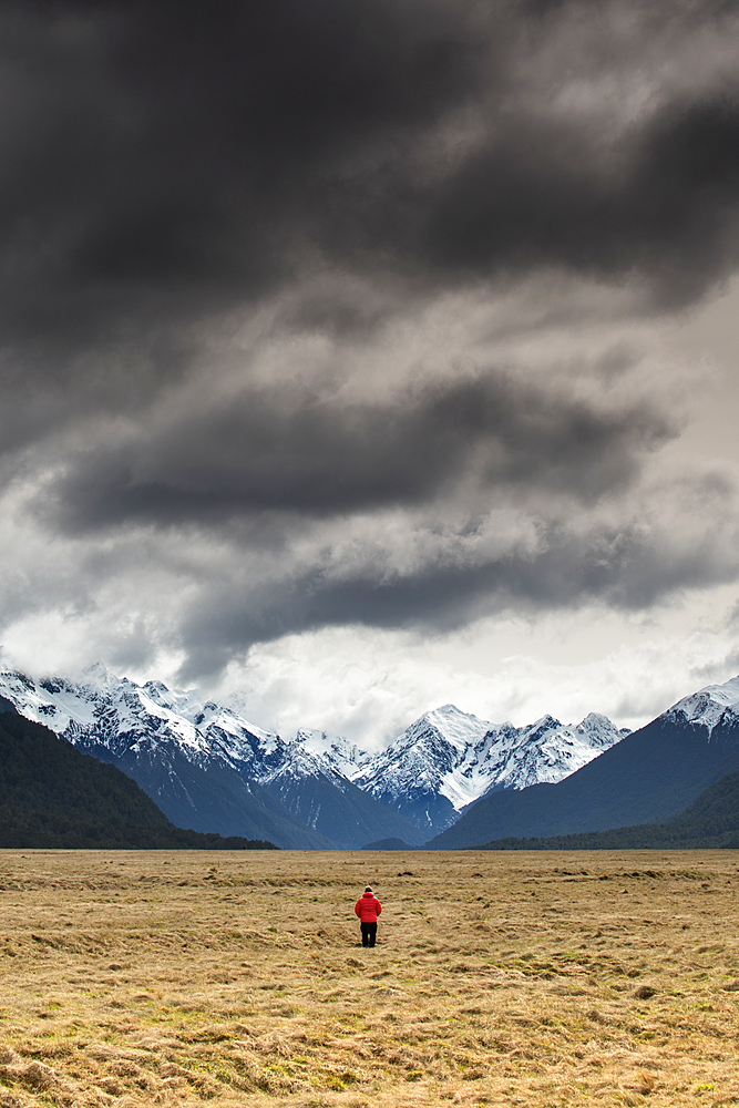 Man in red coat stood looking at snow capped mountains, Fiordland National Park, UNESCO World Heritage Site, South Island, New Zealand, Pacific