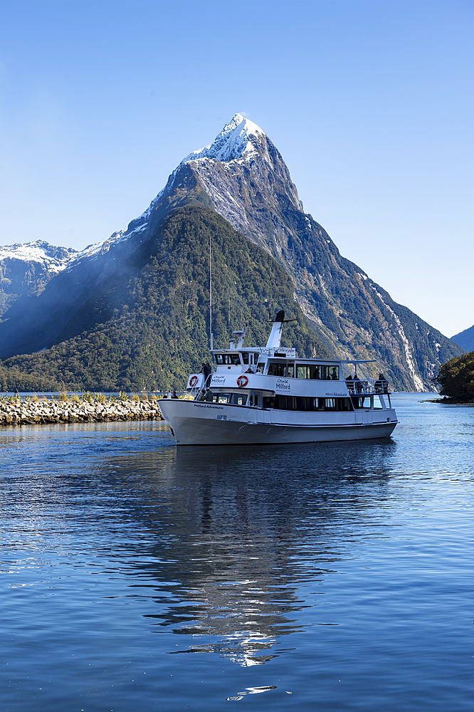 Milford Adventurer Cruise ship at Milford Sound with snow capped Mitre Peak, Fiordland National Park, UNESCO World Heritage Site, South Island, New Zealand, Pacific