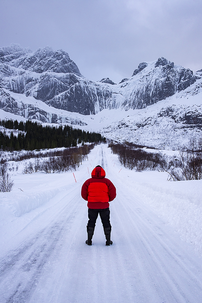 Male stood on snow covered road in arctic winter conditions with mountain back drop, Lofoten, Norway.