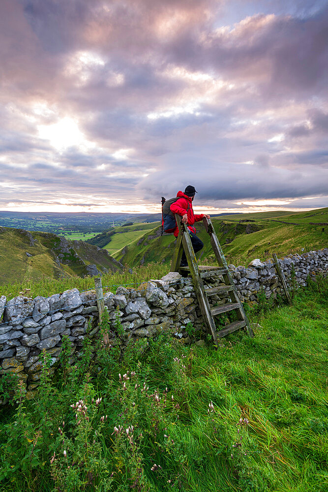 A walker climbing a stile at Winnats Pass, Winnats Pass, Hope Valley, Derbyshire