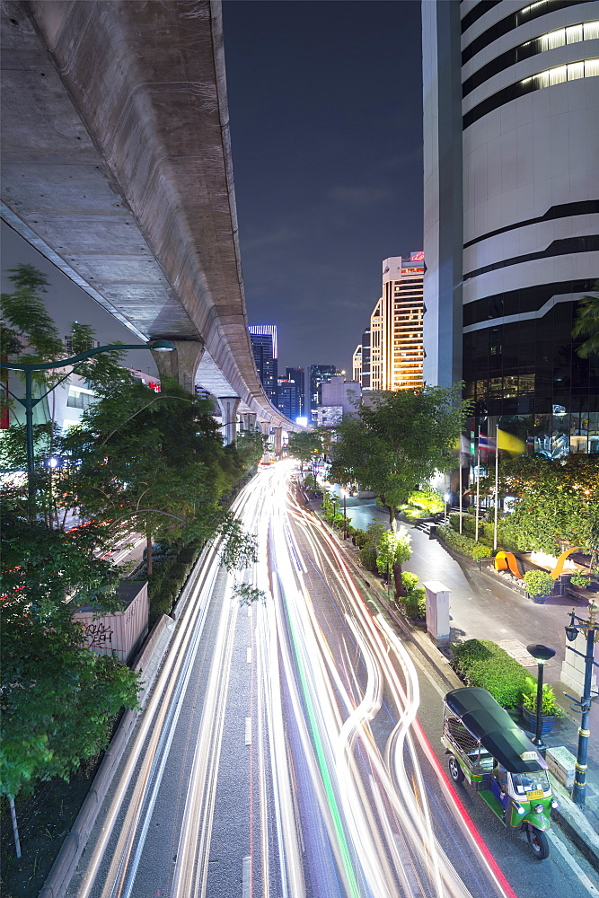 View of elevated skytrain track and traffic light trails on Sukhumvit Road in downtown Bangkok, Thailand, Southeast Asia, Asia