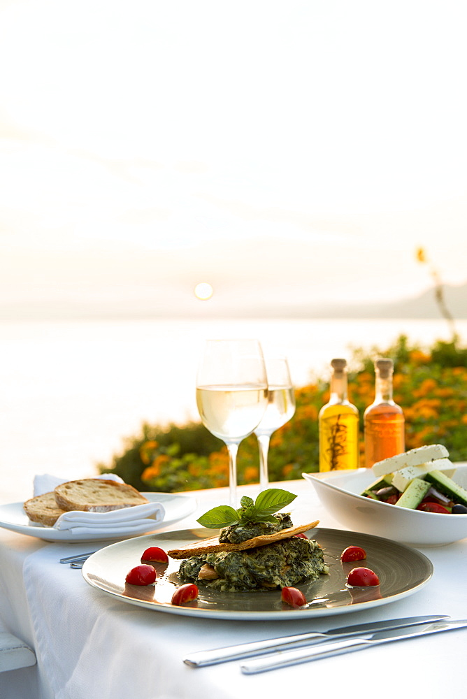 Food at a restaurant with a view over Pefkos Beach beach at sunset, Pefkos, Rhodes, Dodecanese, Greek Islands, Greece, Europe