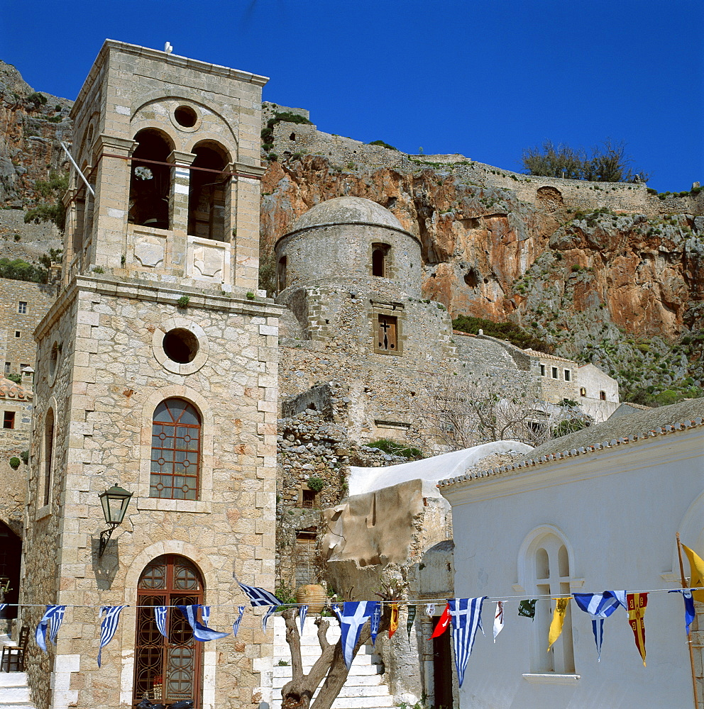 Greek flags and bunting for Independence Day, in front of the bell tower and church at Monemvasia, the Gibraltar of Greece, Greece, Europe