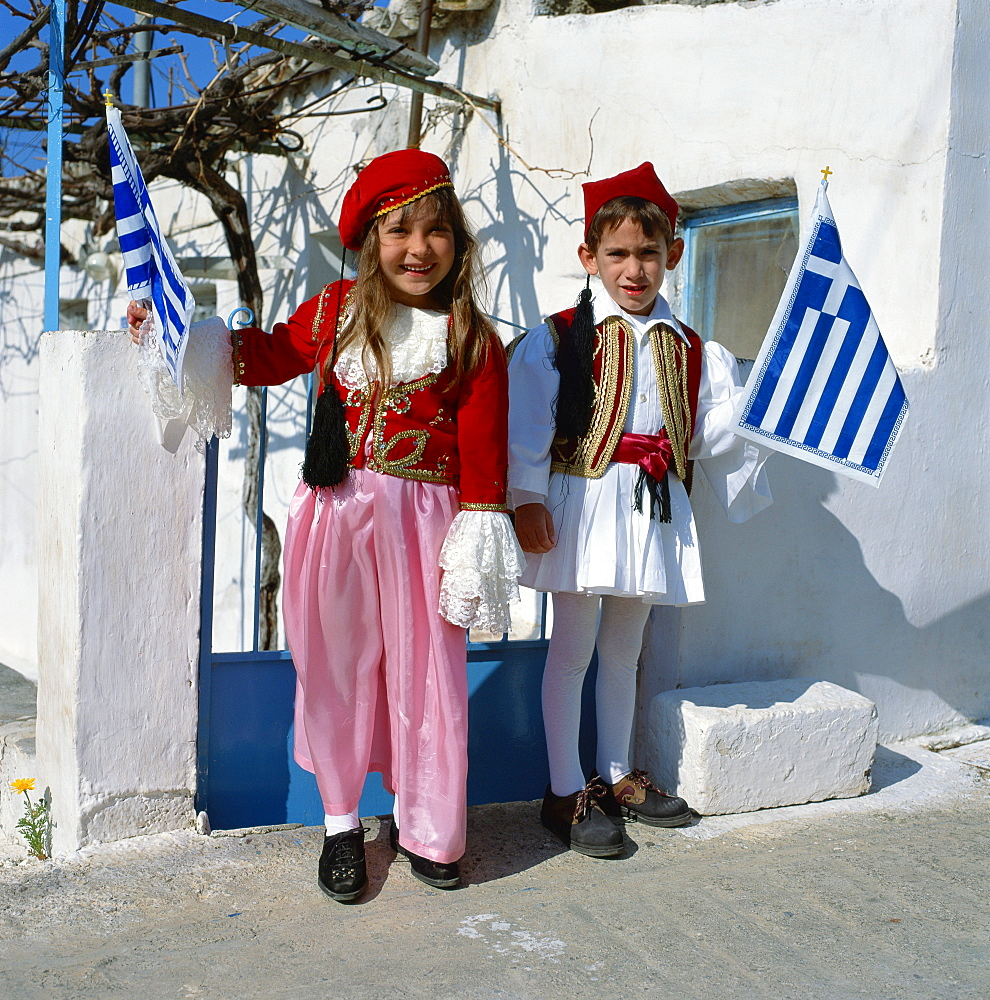 Portrait of two children in national dress carrying flags, celebrating Independence Day, in Greece, Europe